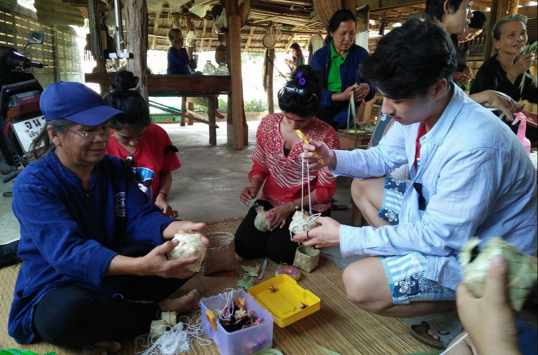 Students making flower strings in Thailand.